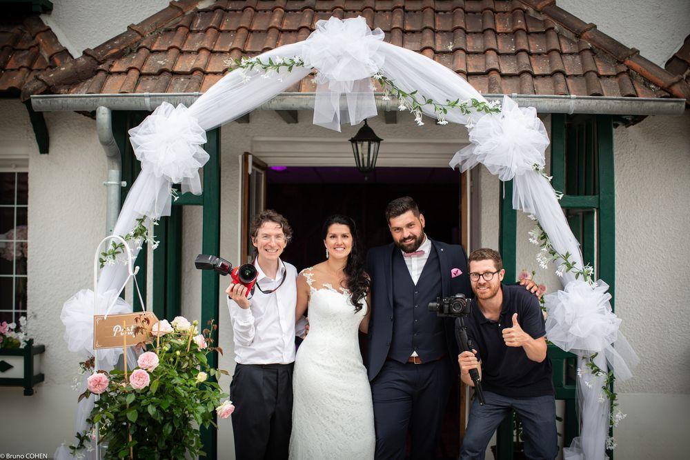 couple de mariés sous une arche de mariage en tulle posant avec Bruno Cohen, photographe et Hugues Rouillot, vidéaste au Manoir des Essarts